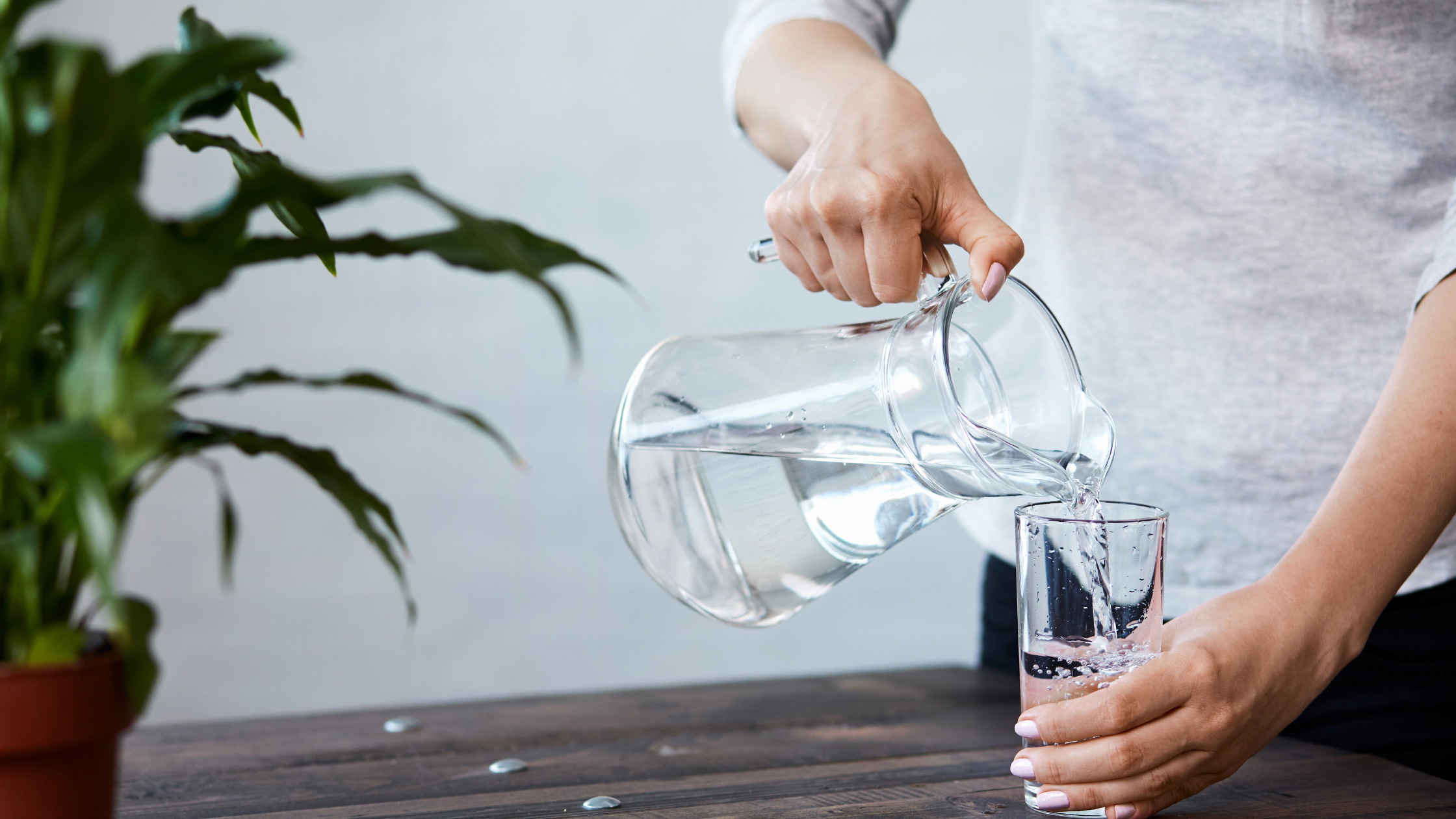 Woman pouring a glass of water. Image: canva