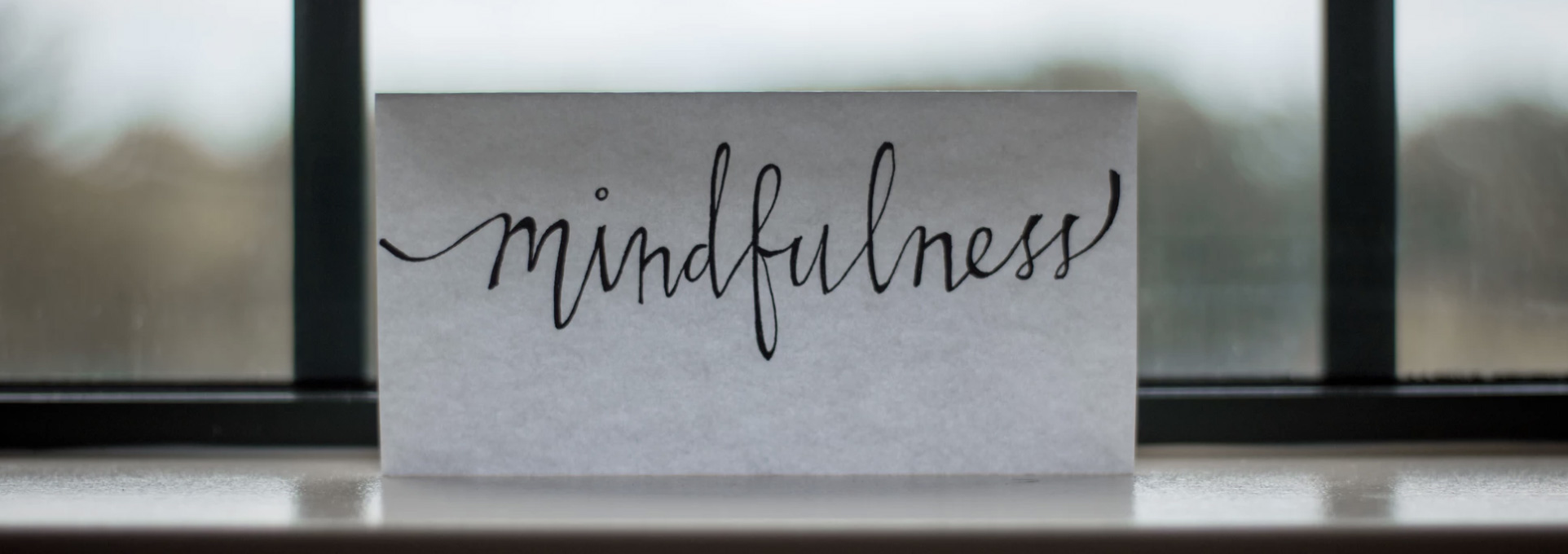 A paper in the window with a mindfulness caption on it