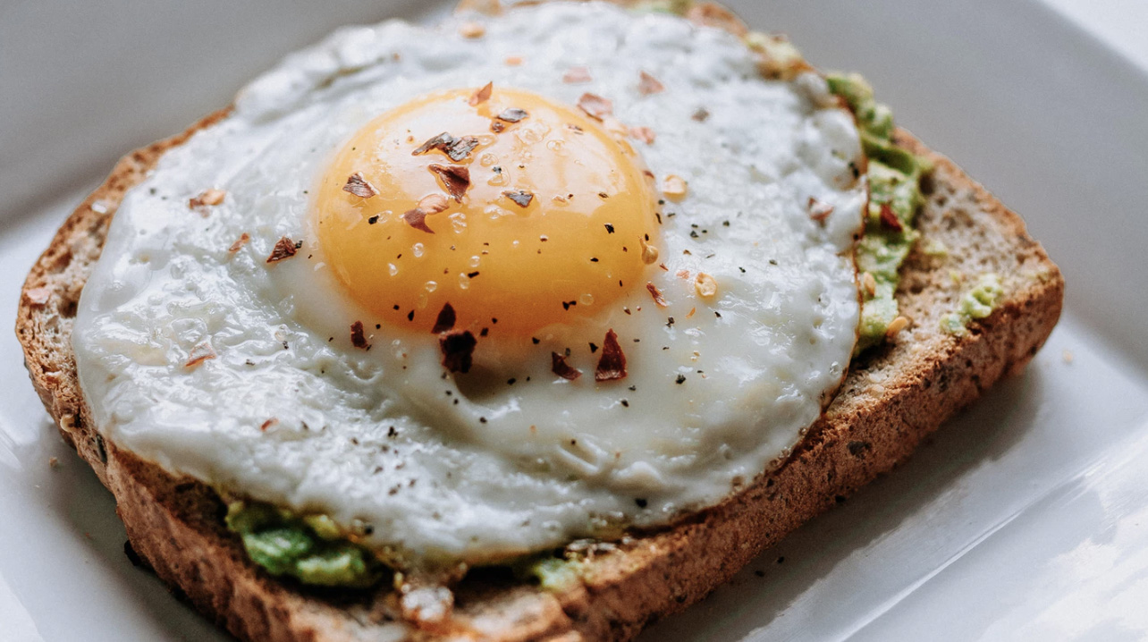 Bread, avocado and fried egg on the top