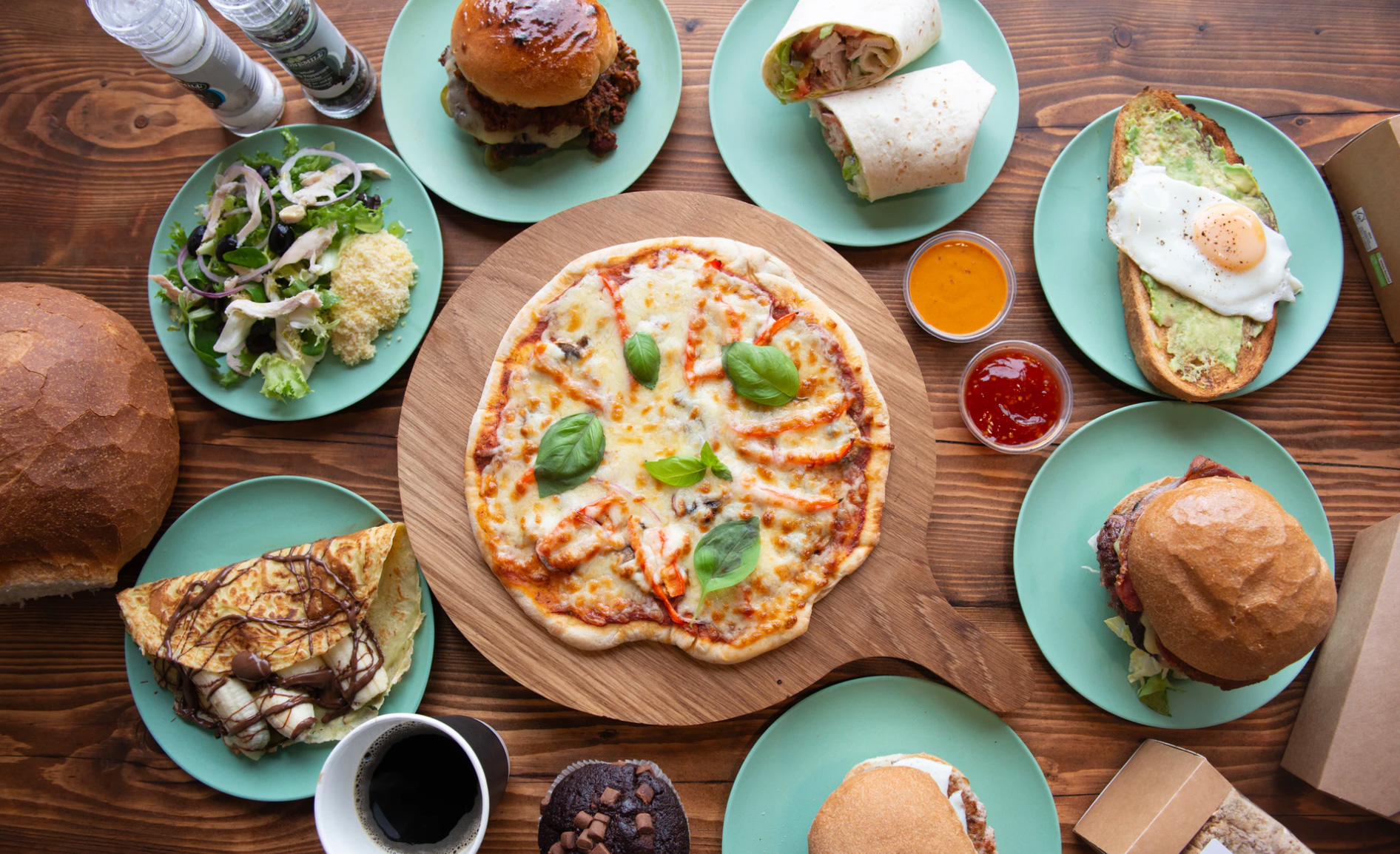 A table with many food selections of pizza, crepes, avocado toast, burgers