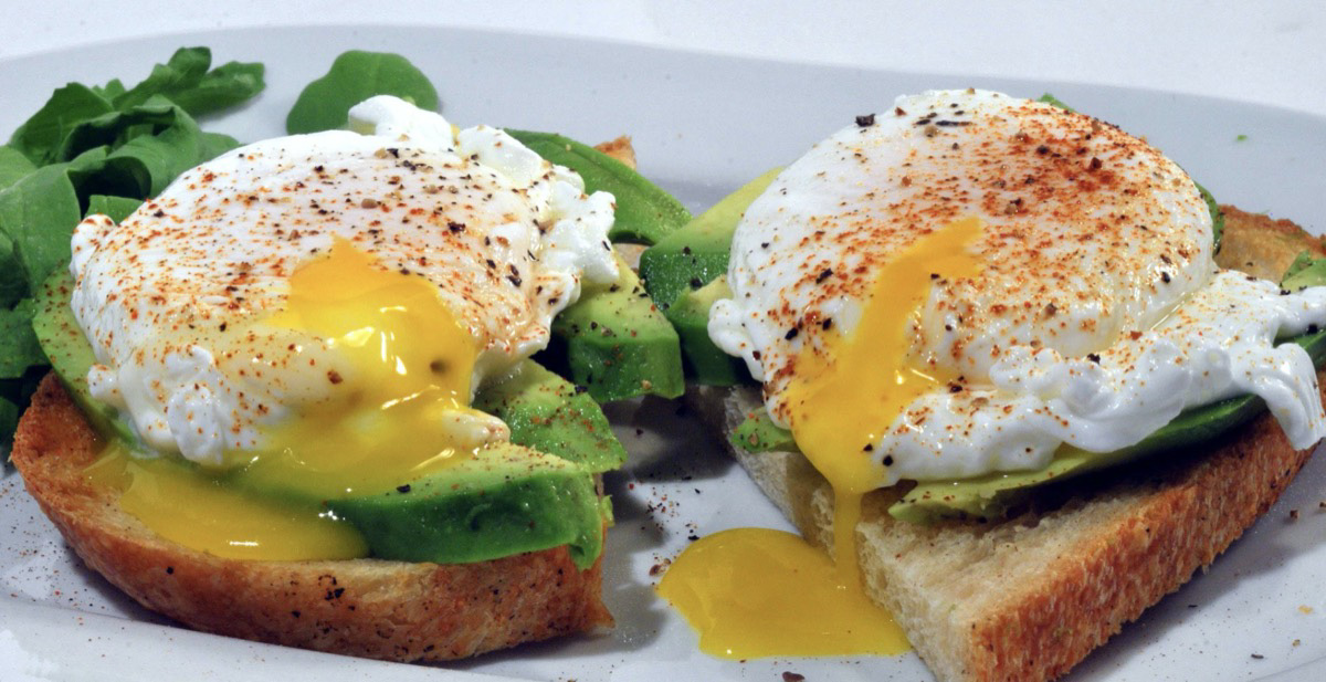 Breakfast sandwich with eggs and avocado.