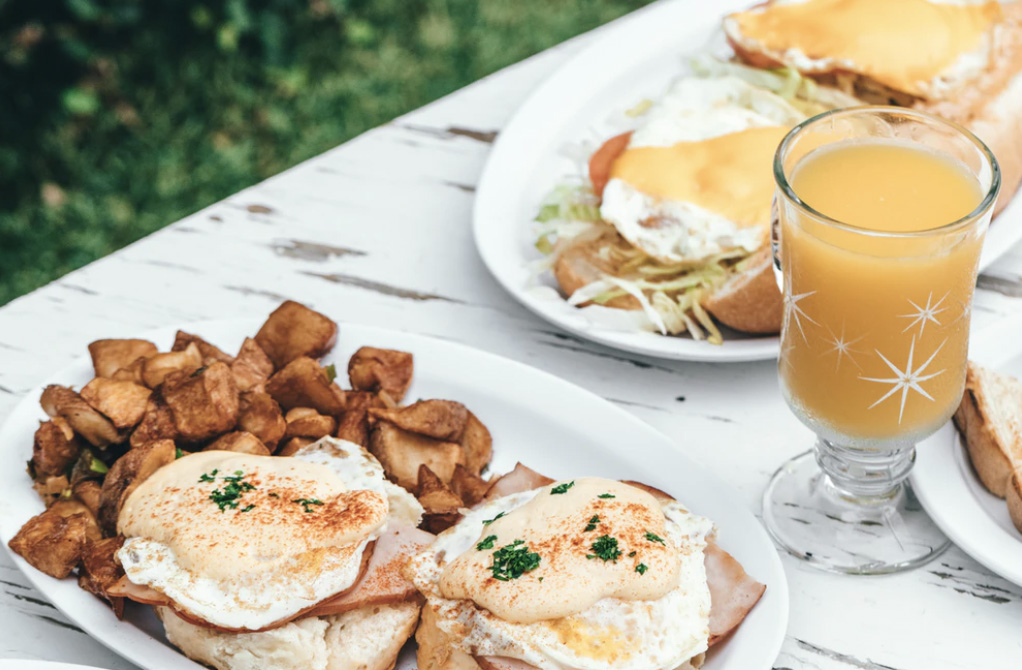 An egg brunch with hash browns and orange juice for more individuals