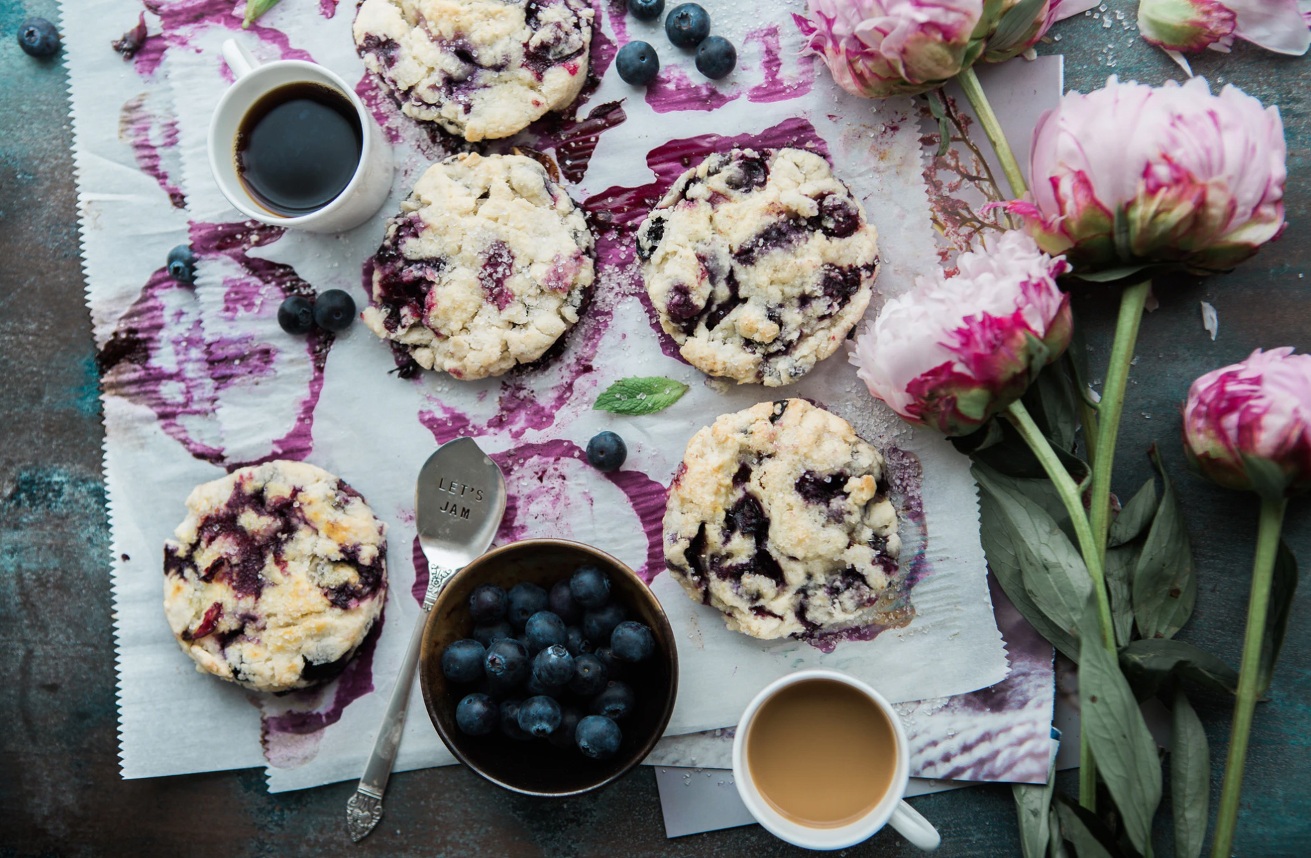 A plate of cranberry and blueberry cookies with peonies