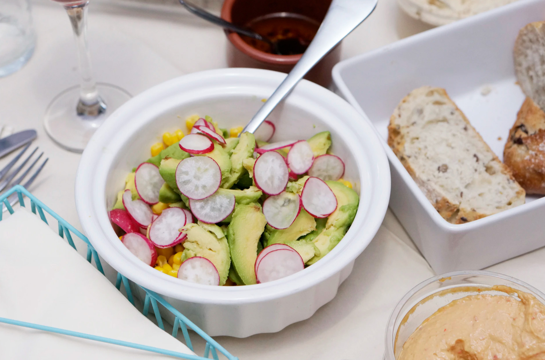 Avocado salad with radish and hummus and homemade bread, image from Unsplash - by Maria Vig