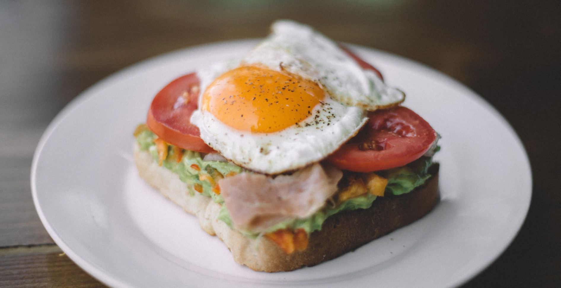 Avocado toast with eggs and tomatoes on a plate