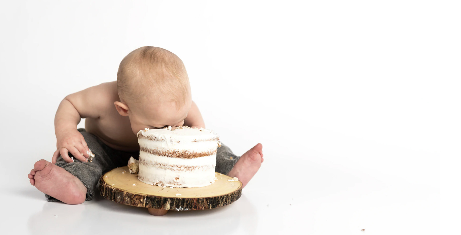 Child eating cake and digging head into it