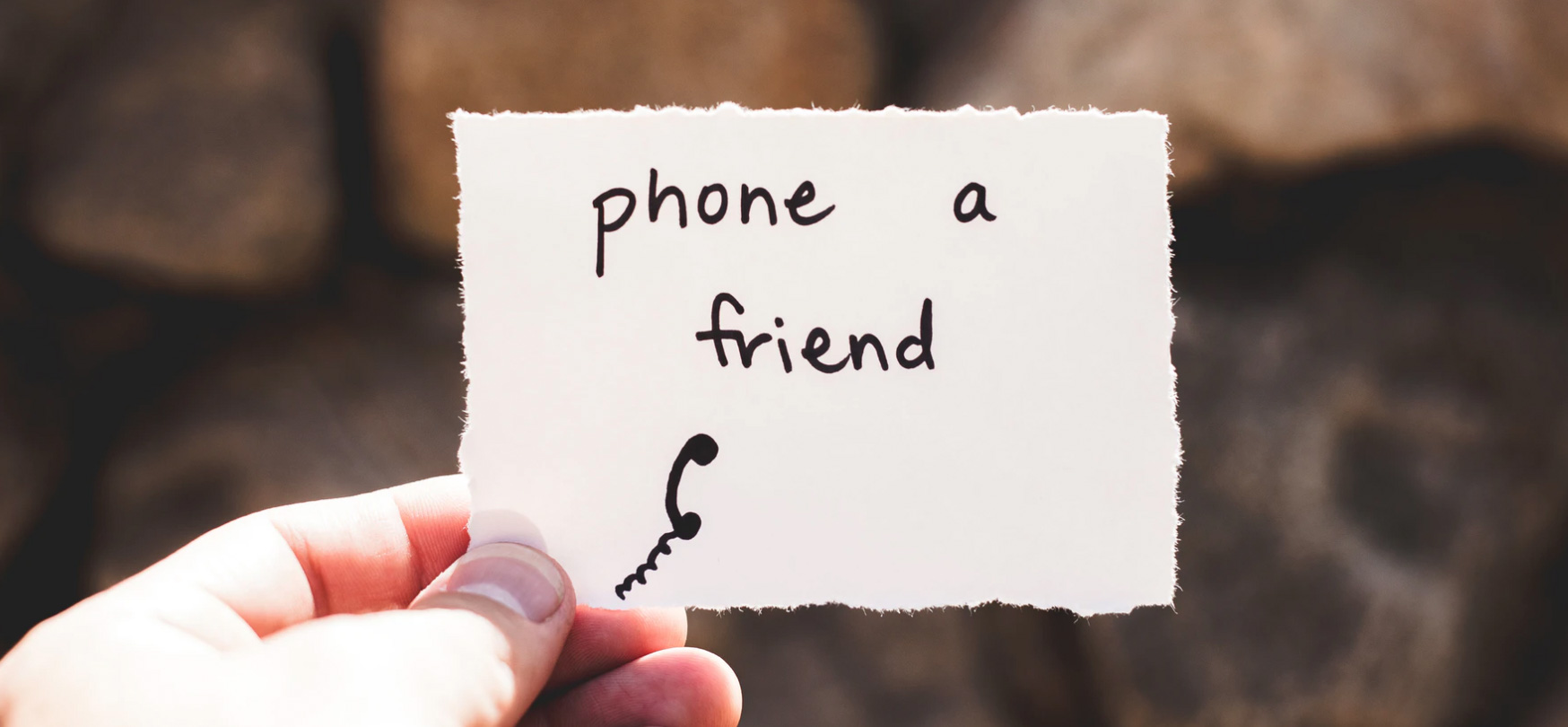 Person holding a piece of paper that says, phone a friend