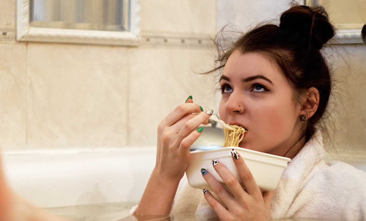 Girl sitting in tub eating a bowl of pasta looking sad.