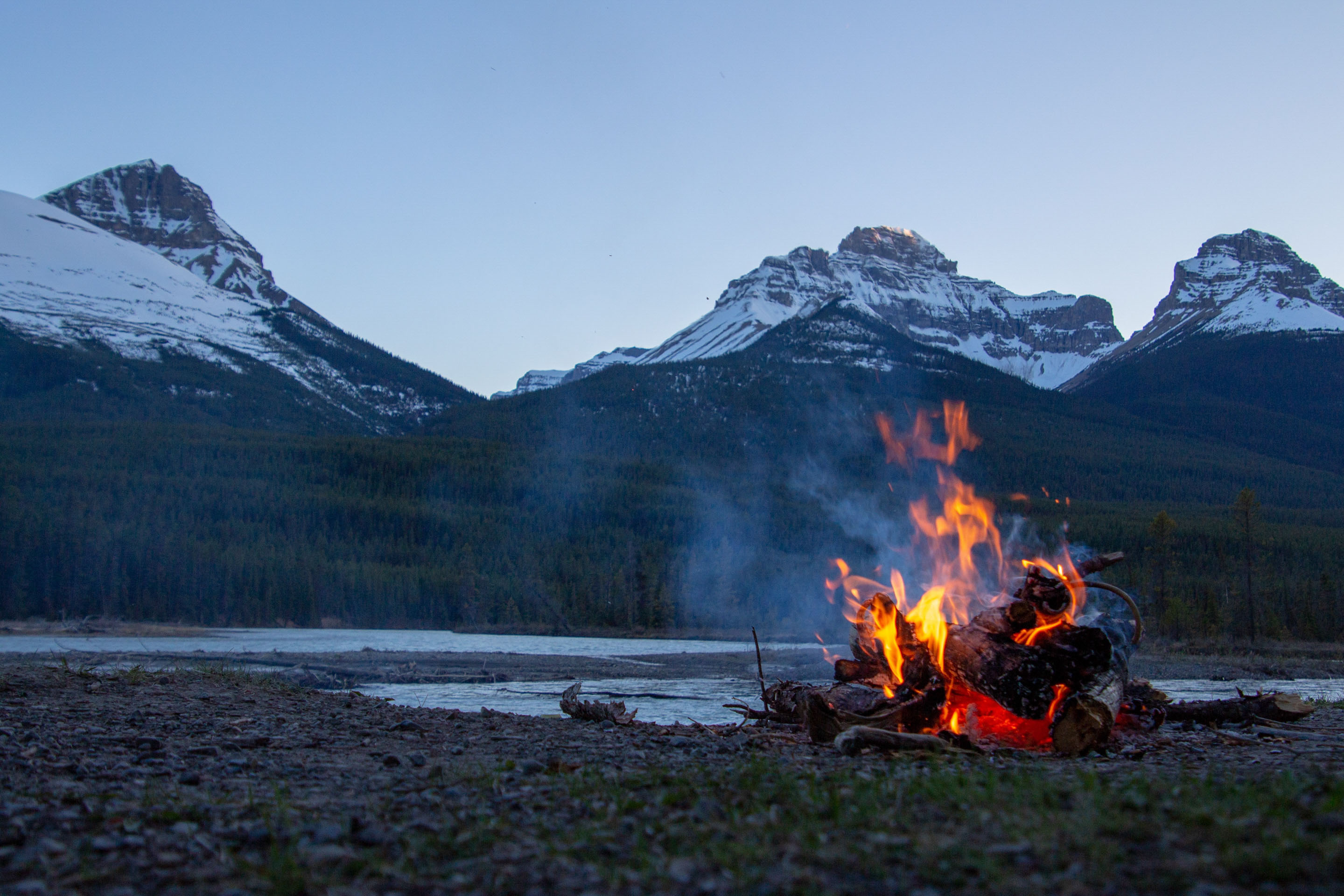 Summer time fire-it in front of mountains. Unsplash - Courtnie Tosana