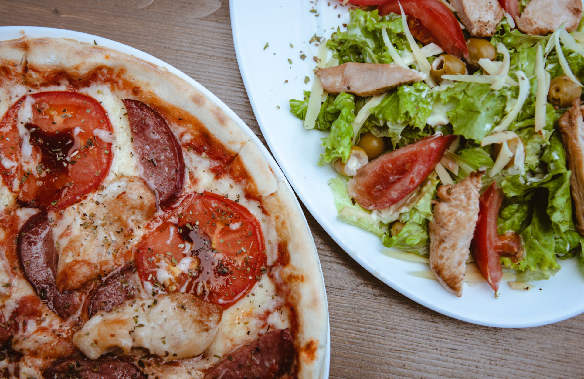 A table with pizza and salad.