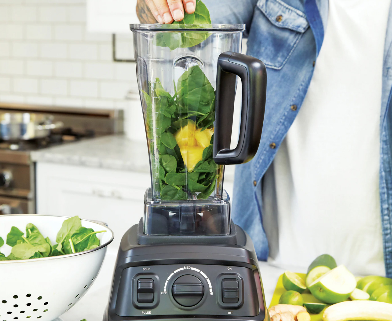 Blender with spinach and fruit to make a smoothie or detox drink