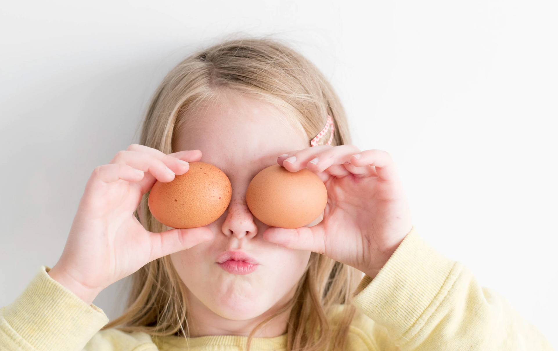 child holding 2 eggs in front of her eyes