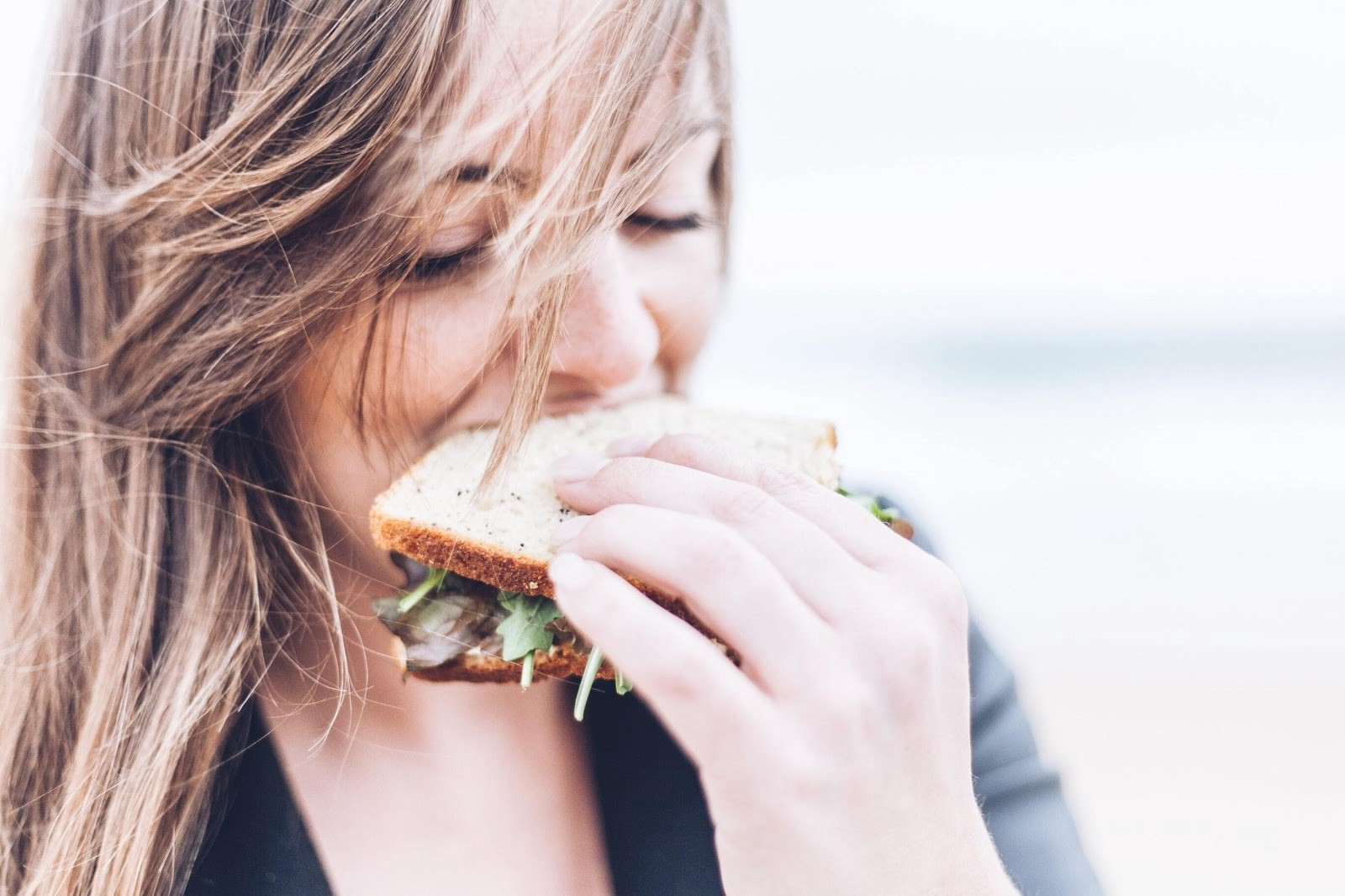 A girl eating a sandwich mindfully