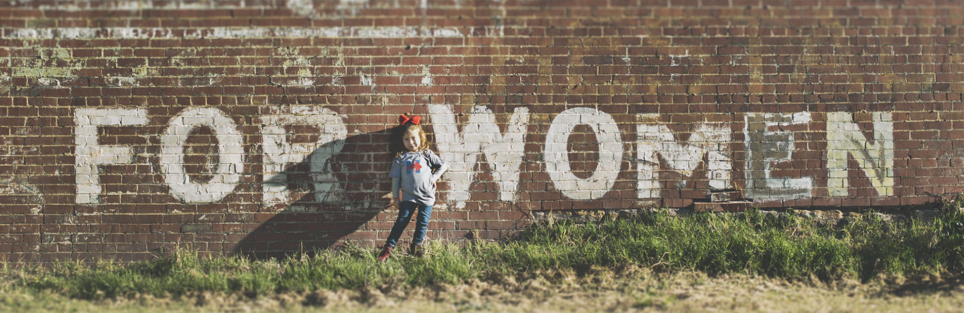 A sign on a brick wall that reads for women with a little girl standing in front of it
