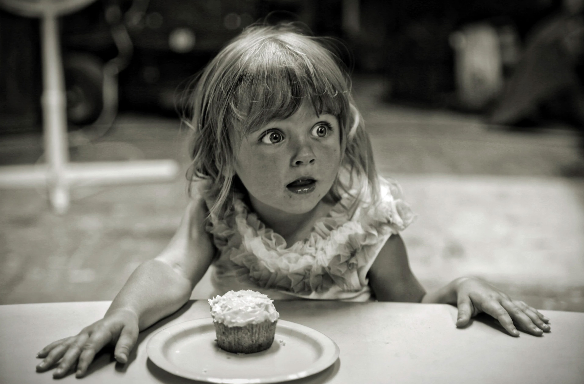Black and white photo with little girl sitting in front of a cupcake and surprised.