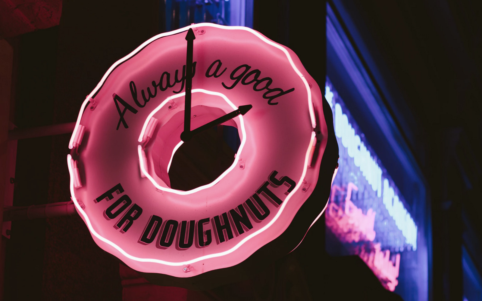 A neon sign of a donut place that says it's always a good time for a doughnuts.