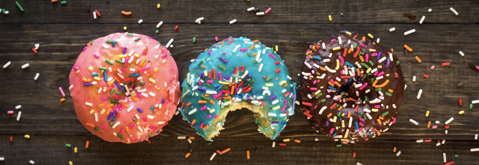 Three donuts with sprinkles on a table next to each other.