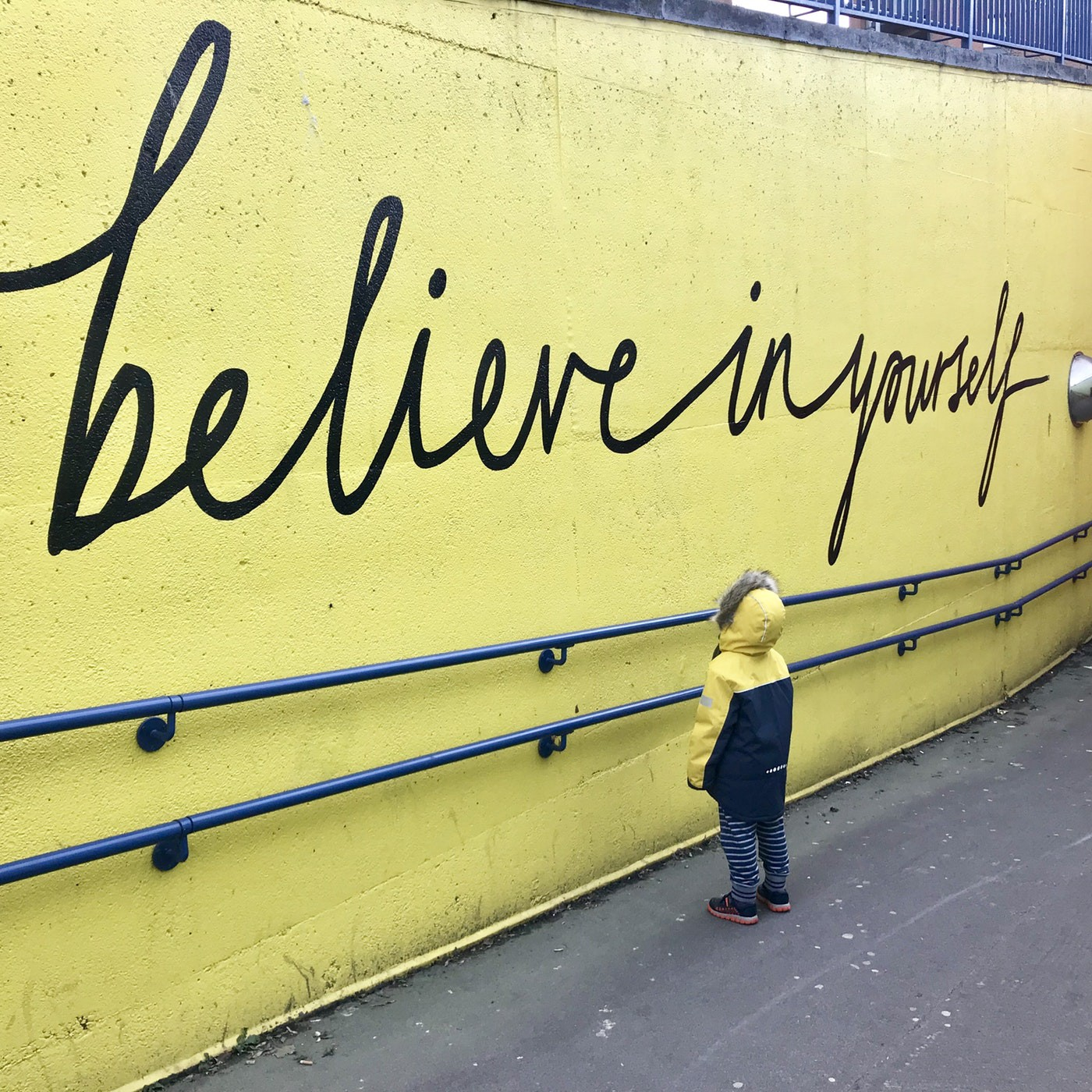 A yellow wall with believe in yourself written on it with a child looking up at it