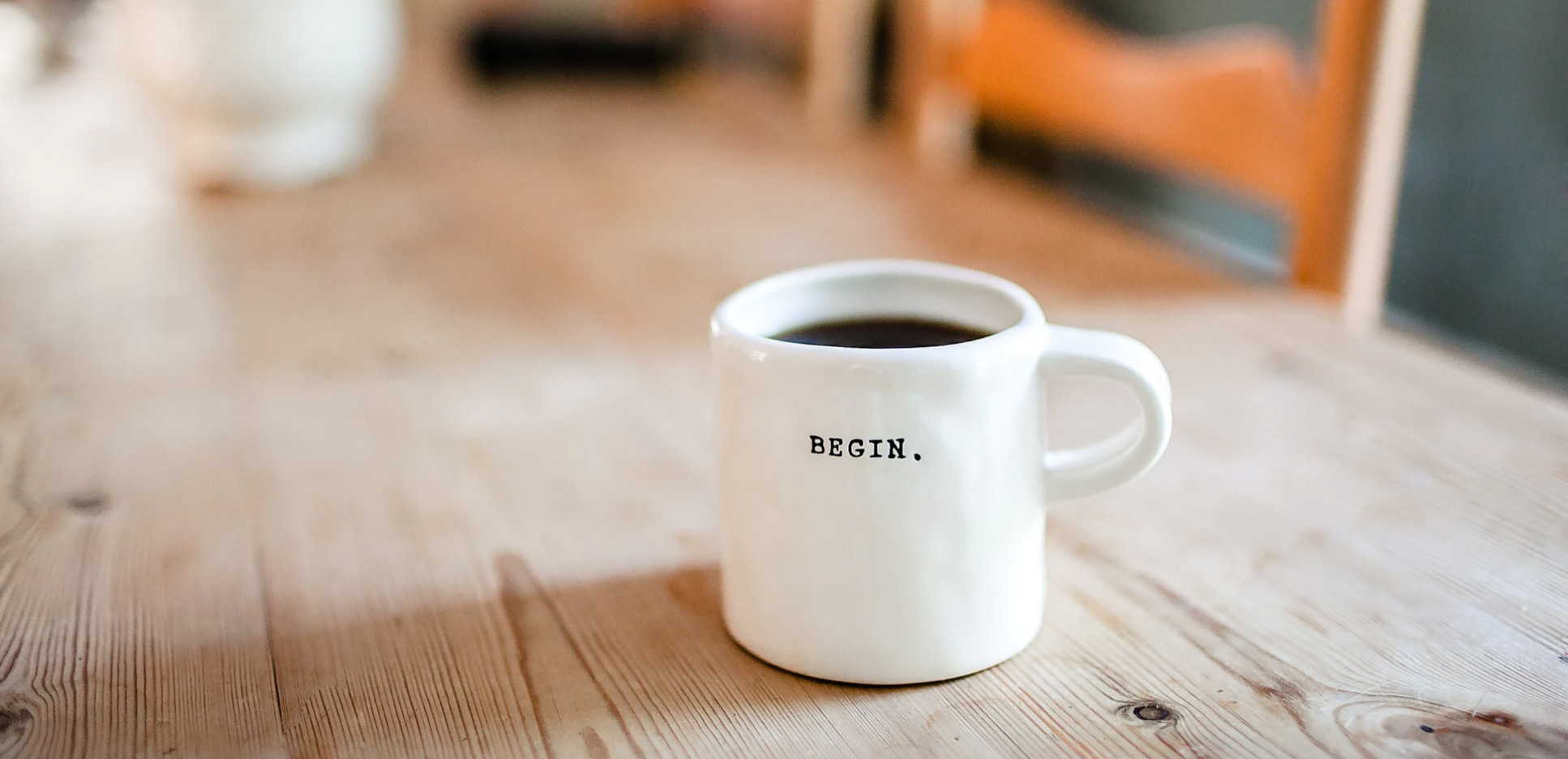 A coffee mug that says begin on it