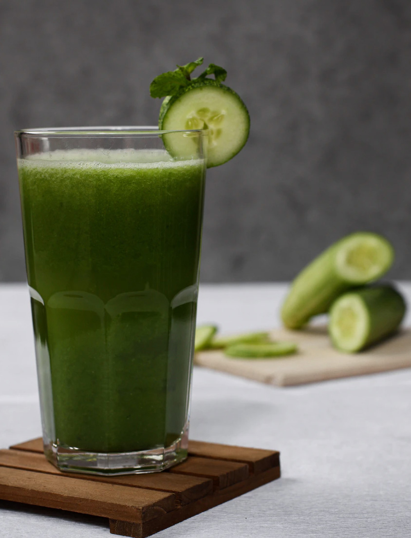 A cup of green juice with cucumbers in the background