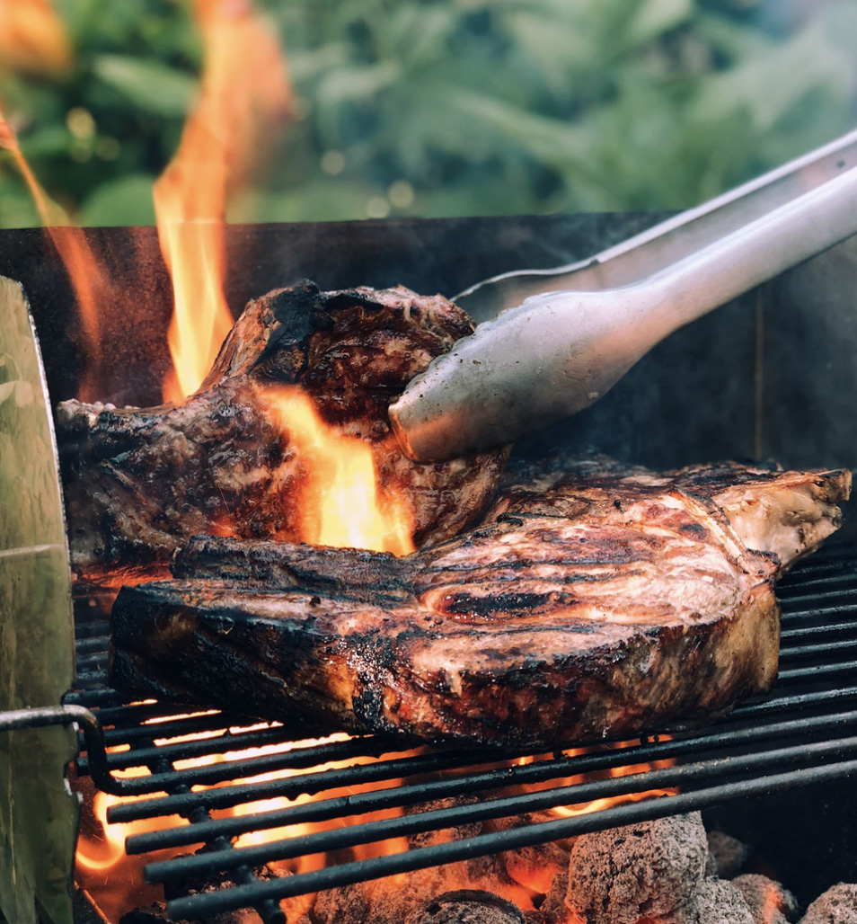 Red meat, steak, being prepared on an open grill with open flames.