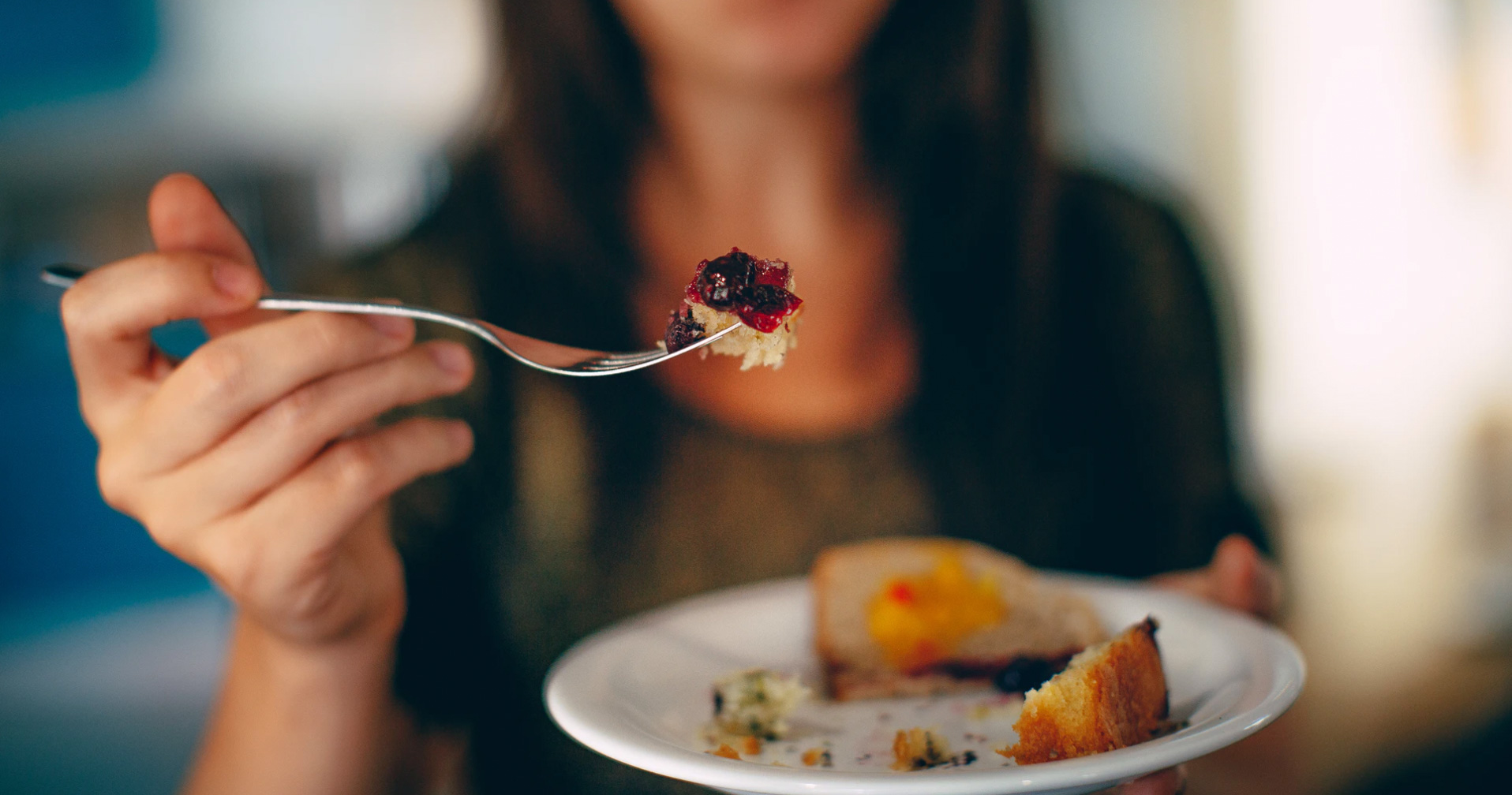 Woman with fork in her hand with food. Unsplash: Helena Lopes