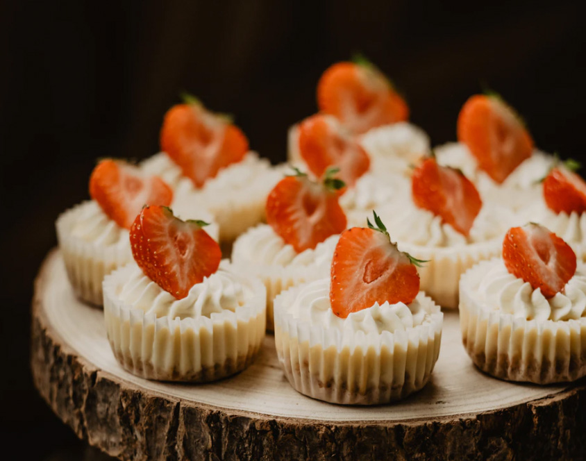 Mini cheesecakes with strawberries being served.