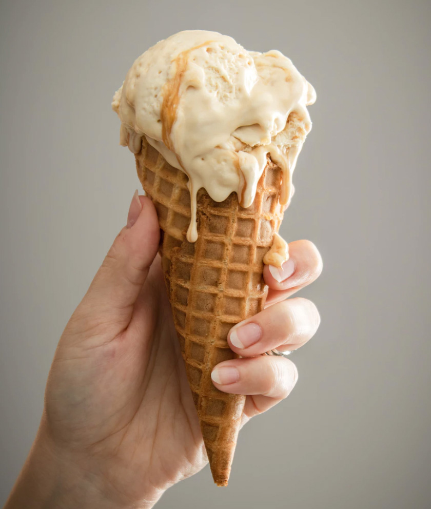 Hand holding an ice cream cone and ice cream.