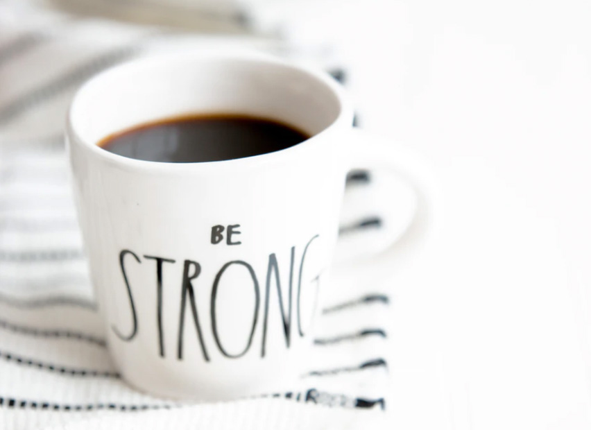 A cup of coffee inside of a mug that says be strong.