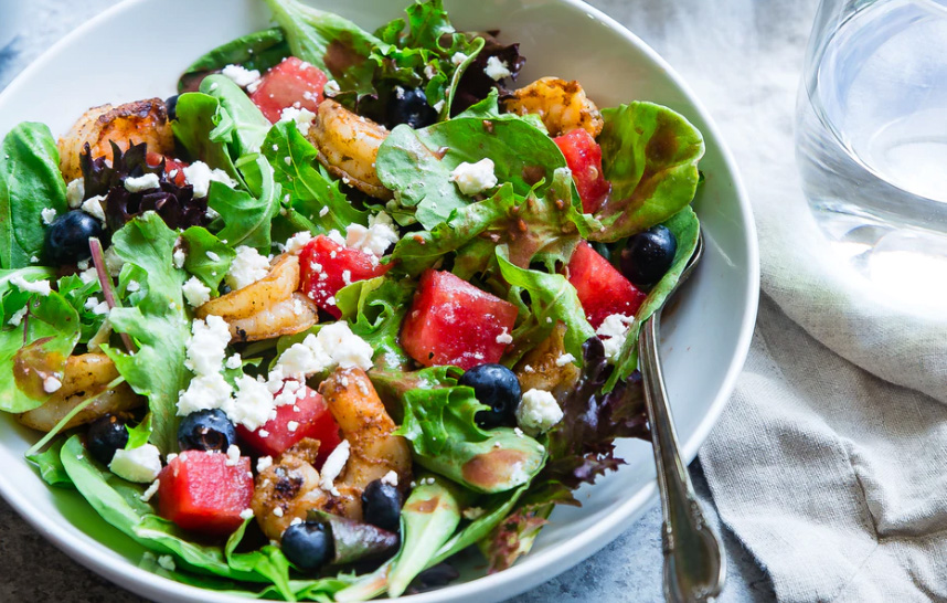 A green salad with fruits and vegetables